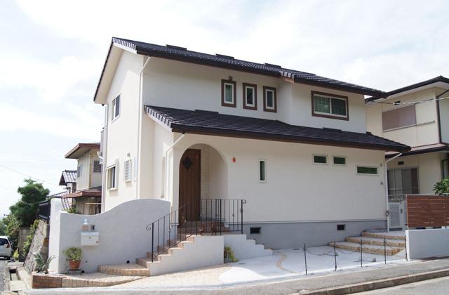 白を基調に手作り感にこだわった外観。玄関ドア前のアーチが印象的だ。軒を深くすることで夏の日射を減らして省エネの住まいを実現するとともに、雨風から外壁を守る効果もある。